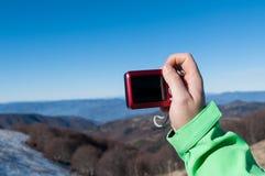 Viandante che prende foto con la macchina fotografica digitale sulla montagna Immagine Stock Libera da Diritti