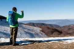 Viandante che prende foto con la macchina fotografica digitale sulla montagna Fotografie Stock Libere da Diritti