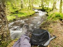 Viandante che riposa nella foresta accanto al fiume Fotografie Stock