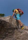 Viandante che scala su una roccia Immagini Stock