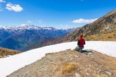 Viandante che si inginocchia e che riposa sulla sommità scenica della montagna Fotografia Stock Libera da Diritti