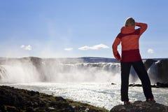 Viandante che si leva in piedi ad una cascata, Islanda della donna Fotografie Stock Libere da Diritti