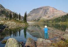 Viandante che si leva in piedi al bordo del lago ring Fotografia Stock Libera da Diritti