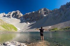 Viandante che si rilassa nel lago blu di elevata altitudine nell'ambiente non contaminato idilliaco coperto una volta dai ghiacci fotografie stock
