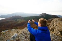 Viandante che si siede e che prende foto di bello paesaggio della montagna con il telefono cellulare Uomo dello scalatore che fot Fotografia Stock