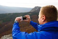 Viandante che si siede e che prende foto di bello paesaggio della montagna con il telefono cellulare Uomo dello scalatore che fot Immagini Stock