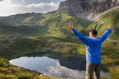 Viandante che sta con le mani sollevate vicino al bello lago della montagna al tramonto Fotografia Stock