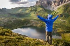 Viandante che sta con le mani sollevate vicino al bello lago della montagna e che gode della vista Fotografia Stock Libera da Diritti
