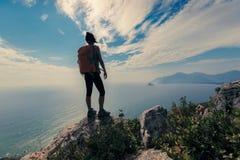 Viandante che sta sul picco di montagna Immagini Stock