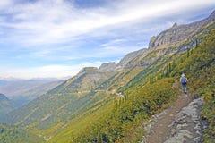 Viandante che viaggia su una traccia alpina a distanza Immagini Stock
