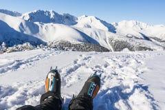 Viandante con gli stivali caldi di alpinismo con i ramponi automatici nel paesaggio di inverno nelle montagne Fotografia Stock