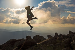 Viandante con lo zaino che salta sopra il cielo di tramonto delle rocce sui precedenti Fotografia Stock