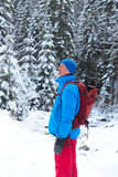 Viandante con lo zaino che sta fra il pino innevato Fotografia Stock