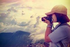 Viandante d'annata di stile che prende foto al tramonto Fotografia Stock