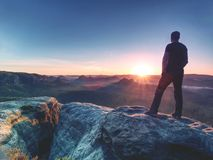 Viandante dell'uomo al picco di montagna Alba piacevole nel paesaggio nebbioso fotografia stock