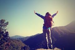 Viandante della donna a braccia aperte sul picco di montagna di alba Immagine Stock Libera da Diritti
