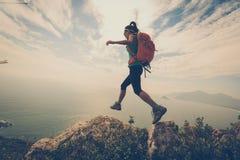 Viandante della donna che fa un'escursione sul picco di montagna Fotografie Stock