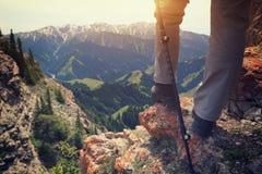Viandante della donna che fa un'escursione sulla scogliera del picco di montagna Immagini Stock