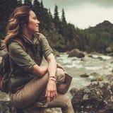 Viandante della donna che si siede sul fiume selvaggio vicino di pietra della montagna Fotografia Stock