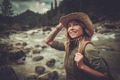 Viandante della donna che sta vicino al fiume selvaggio della montagna Fotografia Stock Libera da Diritti