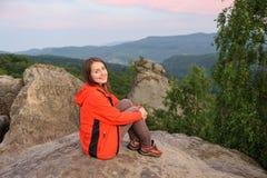 Viandante della donna su grande roccia sopra la montagna immagini stock