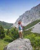 Viandante della donna sul modo al picco di montagna, il giorno soleggiato, contro chiaro cielo blu, spazio per testo Fotografia Stock Libera da Diritti