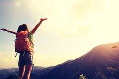 Viandante della giovane donna a braccia aperte al picco di montagna Fotografia Stock