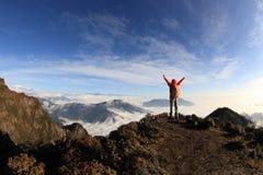 Viandante della giovane donna a braccia aperte sul picco di montagna Fotografie Stock