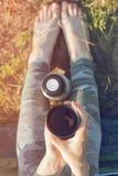 Viandante della ragazza in una tenda e nella tenuta della tazza di tè caldo Montagne e lago nei precedenti Fotografia Stock