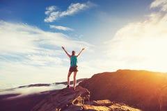 Viandante felice della donna con a braccia aperte al tramonto sul picco di montagna Fotografia Stock Libera da Diritti