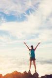 Viandante felice della donna con a braccia aperte al tramonto sul picco di montagna Fotografie Stock