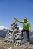 Viandante felice della ragazza che mette le pietre, piccole rocce sulla pila di pietra, su in montagne Immagine Stock Libera da Diritti