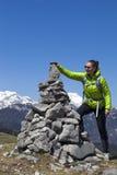Viandante felice della ragazza che mette le pietre, piccole rocce sulla pila di pietra, su in montagne Fotografie Stock Libere da Diritti