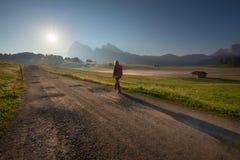 Viandante femminile che cammina al sol levante nelle alpi del sud del Tirolo Fotografia Stock