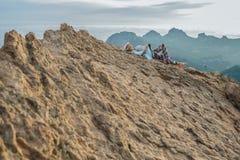 Viandante femminile che riposa sulla cima di un'alta montagna ripida con una macchina fotografica della foto, picco dell'arenaria Fotografia Stock Libera da Diritti