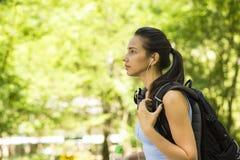 Viandante femminile con lo zaino che cammina sulla traccia della foresta del paese Fotografia Stock Libera da Diritti