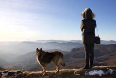 Viandante femminile e suo il cane che guardano orizzonte da apennines ligure Fotografie Stock Libere da Diritti
