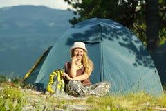 Viandante femminile felice davanti alla tenda dell'accampamento Immagine Stock