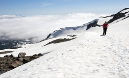 Viandante femminile sopra le nuvole sulla cima nevosa della montagna Fotografia Stock