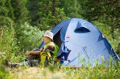 Viandante femminile vicino alla tenda dell'accampamento Fotografia Stock Libera da Diritti