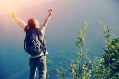 Viandante incoraggiante della donna a braccia aperte al picco di montagna Fotografia Stock Libera da Diritti