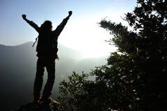 Viandante incoraggiante della donna a braccia aperte al picco di montagna Immagine Stock Libera da Diritti