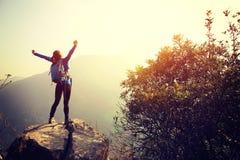 Viandante incoraggiante della donna a braccia aperte al picco di montagna Fotografia Stock