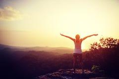 Viandante incoraggiante della donna a braccia aperte al picco di montagna Immagini Stock