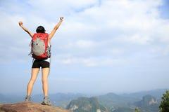 Viandante incoraggiante della donna a braccia aperte al picco di montagna Immagine Stock