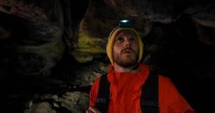 Viandante maschio che esplora una caverna scura 4k video d archivio