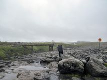 Viandante maschio che fa un'escursione da solo nel paesaggio vulcanico pieno d'ammirazione selvaggio con lo zaino pesante Smania  immagini stock