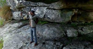 Viandante maschio che guarda tramite il binocolo vicino ad una caverna 4k stock footage