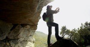 Viandante maschio che prende foto con il telefono cellulare vicino ad una caverna 4k archivi video