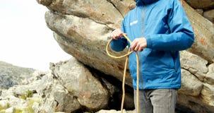 Viandante maschio che tiene una corda in campagna 4k video d archivio